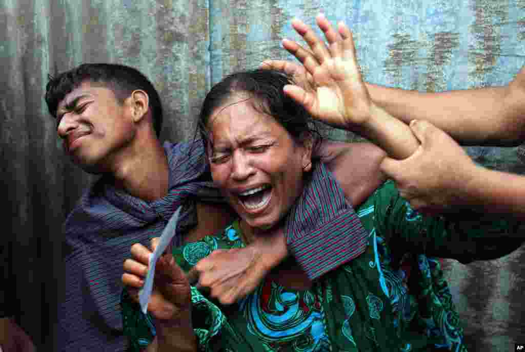 Munni, a woman whose daughters are missing, cries as rescuers search the River Padma in Munshiganj district, Bangladesh, Monday, Aug. 4, 2014.