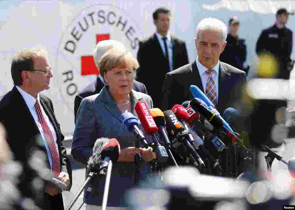 Heidenau major Juergen Opitz, German Chancellor Angela Merkel and Saxony State Prime Minister Stanislaw Tillich (left to right) arrive for statements after their visit to an asylum center in the eastern German town of Heidenau, near Dresden, Aug. 25, 2015.