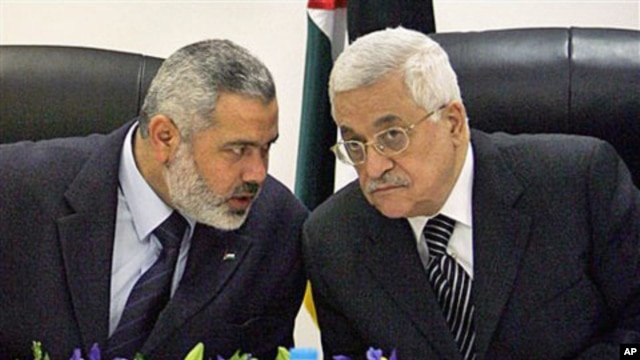 Palestinian Authority President Mahmoud Abbas, right, and Palestinian Prime Minister Ismail Haniyeh of Hamas, left, speak as they head the first cabinet meeting of the new coalition government at Abbas' office, in Gaza City, March 2007 (file photo)