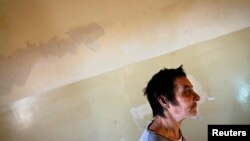 FILE - A patient is seen walking a hallway at a mental health institution in the Balkans.