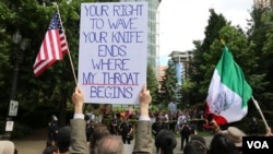 Protesters hold signs as they face off in Portland. (R. Taylor/VOA)