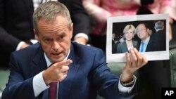 Lãnh đạo đảng đối lập Úc Bill Shorten cầm tấm ảnh chụp giữa Ngoại trưởng Julie Bishop và tỷ phú Trung Quốc Hoàng Hướng Mặc trong khi chất vấn ở Hạ viện tại Canberra ngày 14/6/2017.