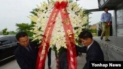 고 김대중 전 대통령의 서거 5주기를 하루 앞둔 17일 개성공단에서 북측 관계자들이 김정은 국방위원회 제1위원장 명의의 조화를 옮기고 있다.