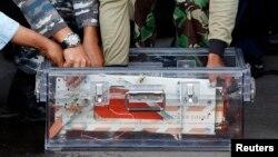 El grabador de datos de vuelo de AirAsia QZ8501 es colocado en un contenedor tras su arribo a la base aérea en Indonesia.