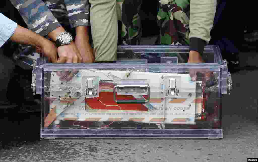 The flight data recorder from AirAsia QZ8501 is placed into a container upon its arrival at the airbase in Pangkalan Bun, Central Kalimantan January 12, 2015.
