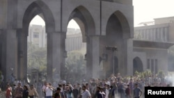 Protesters are seen amid remnants of teargas smoke during clashes with riot police at al-Azhar University in Cairo October 20, 2013.