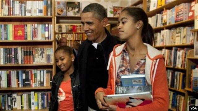 Obama dan dua putrinya Sasha dan Malia berbelanja di toko 'Kramerbooks' di Washington (26/11).