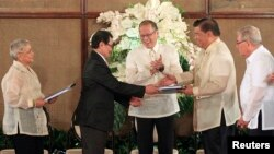 FILE - Philippine President Benigno Aquino, center, applauds as Moro Islamic Liberation Front chief negotiator Mohagher Iqbal, second from left, shakes hands with Senate President Franklin Drilon, second from right, at the presidential palace in Manila, September 10, 2014.