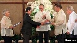 Tổng thống Philippines Benigno Aquino (giữa) hoan nghênh khi Trưởng đoàn đàm phán Mặt trận Giải phóng Hồi giáo Moro (MILF) Mohagher Iqbal (thứ 2-bên trái) bắt tay với Chủ tịch Thượng viện Franklin Drilon (thứ 2-bên phải) trong buổi lễ bàn giao dự thảo Luật cơ bản Bangsamoro (BBL).