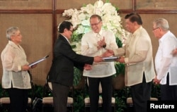 FILE - Philippine President Benigno Aquino (C) applauds as Moro Islamic Liberation Front (MILF) chief negotiator Mohagher Iqbal (2nd L) shakes hands with Senate President Franklin Drilon (2nd R) during the turnover ceremony of the draft Bangsamoro Basic Law (BBL) at the presidential palace in Manila, September 10, 2014.