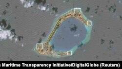 រូបភាពពីលំហអាកាសរបស់អង្គការ CSIS Asia Maritime Transparency Initiative បង្ហាញឲ្យឃើញអ្វីហាក់ដូចជាកាំភ្លើងប្រឆាំងយន្តហោះ និងប្រហែលជាប្រព័ន្ធអាវុធនៅលើកោះសិប្បនិមិត្ត Subi Reef។ រូបថតនេះបញ្ចេញកាលពីថ្ងៃទី១៣ ខែធ្នូ។