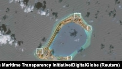 A satellite image shows what CSIS Asia Maritime Transparency Initiative says appears to be anti-aircraft guns and what are likely to be close-in weapons systems (CIWS) on the artificial island Subi Reef in the South China Sea in this image released on Dec