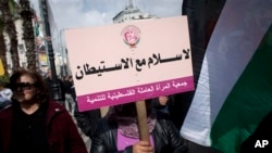 """Palestinian protester holds placard with Arabic writing that says """"no peace with settlements, the Palestinian Women Labor Association,"""" anti-peace talks rally, Ramallah, March 19, 2014."""