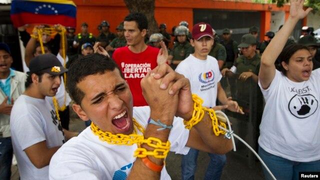 Un grupo de estudiantes se encadenan en señal de protesta cerca a la embajada de Cuba y exigen a la isla que no interfiera en el gobierno venezolano.