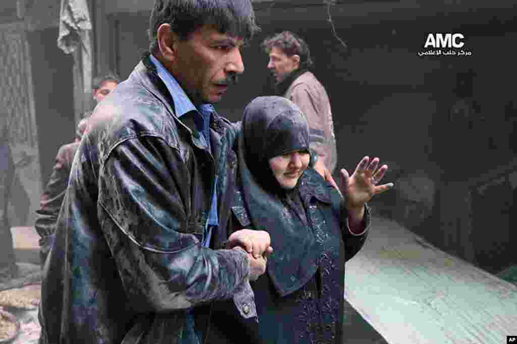 A Syrian man helps a survivor out of a damaged building following an airstrike by Syrian warplanes, Aleppo, April 6, 2014.
