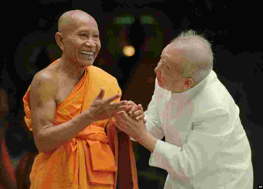 Then King Sihanouk bids goodbye to a Buddhist monk at a temple in Siem Reap, northern Cambodia, September 1,1997.
