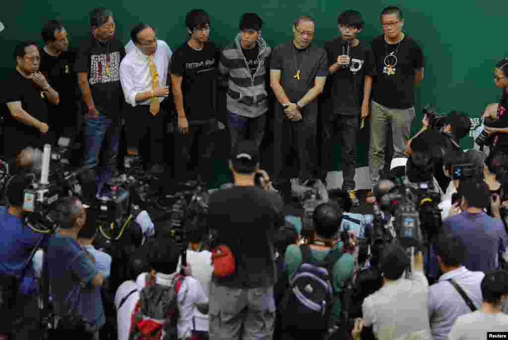 Joshua Wong, second right, leader of the student movement, talks to the media as protesters block areas around the government headquarters office in Hong Kong, Oct. 9, 2014.
