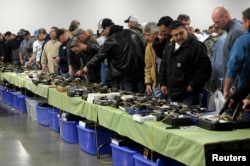 FILE - People look over a table of handguns for sale at a gun show in Kansas City, Missouri, Dec. 22, 2012.