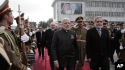 Indian Prime Minister Narendra Modi, left, is escorted by Afghan Chief Executive Abdullah Abdullah as he leaves Kabul at the city's airport, Dec. 25, 2015.
