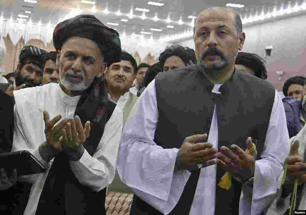 Hashmat Karzai (right), cousin of Afghan President Hamid Karzai, and Afghan presidential candidate Ashraf Ghani pray during a presidential campaign in Kandahar, June 6, 2014.