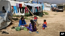 叙利亚妇女在黎巴嫩贝卡谷地巴埃利亚斯镇一个难民营的帐篷外为家人准备饭食(2016年3月29日)