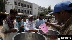 Warga menerima air minum dari sukarelawan di meja yang digelar di luar Jinnah Postgraduate Medical Center (JPMC) di tengah panas terik di Karachi, Pakistan (23/6). (Reuters/Akhtar Soomro)