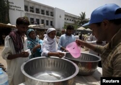 People receive drinking water from a volunteer at a stall, set up outside Jinnah Postgraduate Medical Center (JPMC) during intense hot weather in Karachi, Pakistan, June 23, 2015.