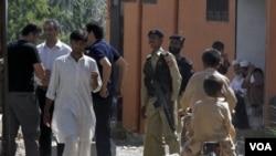 Polisi Pakistan berjaga-jaga di sekitar lokasi bekas tempat tinggal Osama bin Laden di Abbottabad. Ke-3 isteri Osama kini berada dalam tahanan polisi Pakistan.