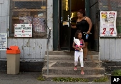 An anti-violence sign, created by former gang members, hangs on a window of a corner convenience store where woman and her daughter finished shopping, Aug. 21, 2017, in the South Side neighborhood of Syracuse, N.Y.