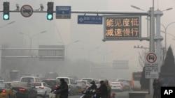 """Una señal de tránsito en Beijing dice """"Baja visilidad, reduzca la velocidad"""" en un día de alta contaminación, el lunes, 30 de noviembre de 2015."""