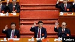 中国共产党第十九次全国代表大会闭幕式上,中共总书记习近平和前总书记江泽民、胡锦涛等人举手表决(2017年10月24日)。