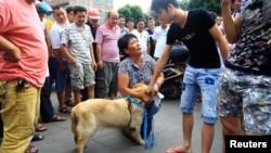 Một nhà hoạt động quỳ xuống để xin mua lại một con chó nhằm ngăn nó khỏi bị làm thịt tại Ngọc Lâm, khu tự trị Quảng Tây.