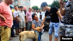 An animal activist kneels down as she offers to buy a dog from a vendor, second right, to stop it from being eaten ahead of the annual dog meat festival in Yulin, Guangxi Zhuang Autonomous Region, June 20, 2014.