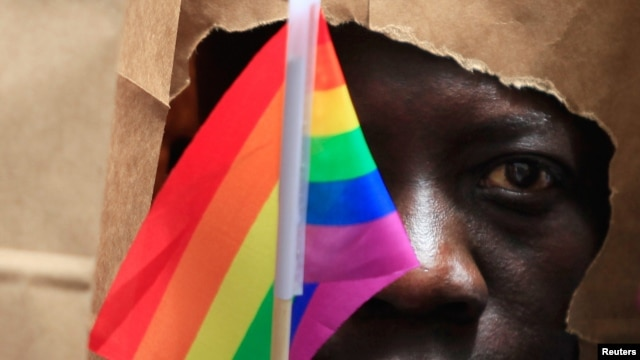 FILE - An asylum seeker from Uganda covers his face with a paper bag to protect his identity as he marches at a Gay Pride Parade in Boston, Massachusetts, June 8, 2013.