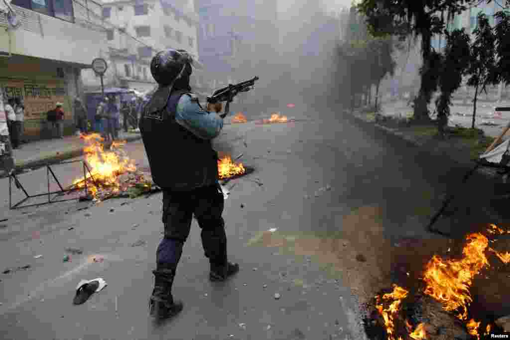A police officer shoots rubber bullets during a clash with activists of Hifazat-e-Islam in front of the national mosque in Dhaka, May 5, 2013.