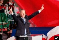 President Andrzej Duda flashes victory signs after voting ended in the presidential election in Lowicz, Poland, Sunday, June 28, 2020.