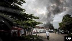 Un homme se dirige vers la fumée d'un incendie dans l'entrepôt de la Commission électorale nationale indépendante (CENI) le 13 décembre 2018 à Kinshasa.