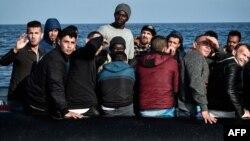 Les migrants réagissent alors que le bateau de sauvetage du MV Aquarius s'approche de leur bateau en caoutchouc à quelque 50 kilomètres de la côte libyenne le 12 mai 2018.