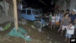 Warga berkumpul di depan rumah yang runtuh di Cagayan De Oro, Filipina, menyusul gempa berkekuatan 7,6 skala Richter. (Foto: AP)