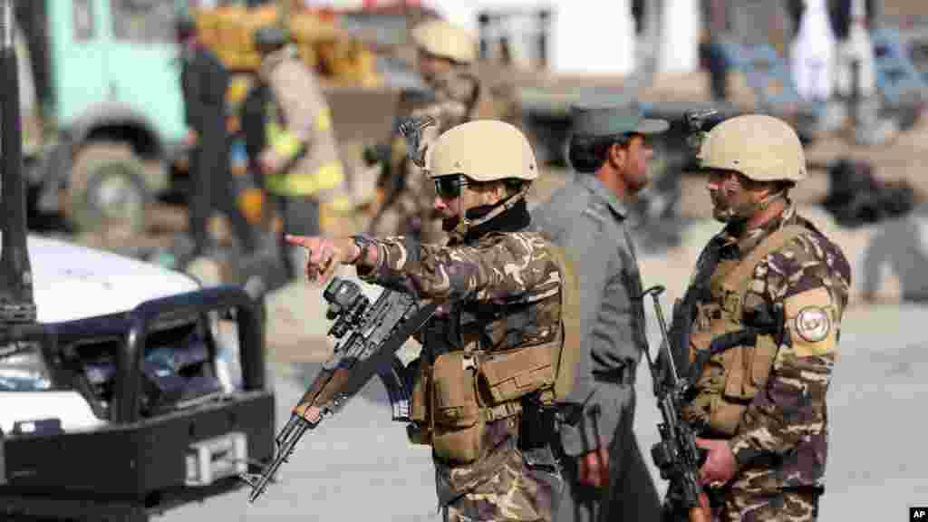 Afghan security forces inspect the site of a suicide attack in Kabul, Afghanistan, Nov. 27, 2014.