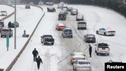 Petugas Kepolisian Charlotte Mecklenburg berupaya membantu mengarahkan para pengendara saat hendak mengemudi melewai bukit yang tertutup salju di Charlotte, North Carolina (12/2).