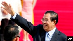 Cambodian Prime Minister Hun Sen waves to the crowd as he arrives at Clark International Airport, north of Manila, Philippines Saturday, Nov. 11, 2017.