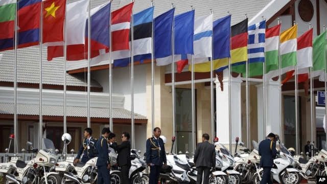 Lao police officials stand next to flags of various nations on display at Wattay International Airport in Vientiane, Laos, Sunday, Nov. 4, 2012.