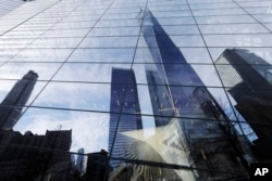 One World Trade Center is reflected in the windows of the National September 11 Museum, Thursday, March 30, 2017, in New York. (AP Photo/Mark Lennihan)