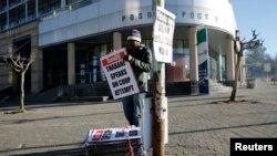 A worker hangs posters displaying newspaper headlines, in the capital Maseru, August 31, 2014.