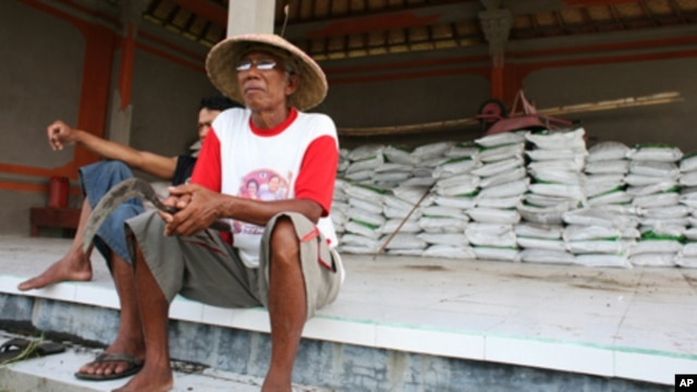 Farmers in Indonesia sitting in front of processed rice that is ready to be sold. Economists say rice farmers living below the poverty line could be the most vulnerable to the impact of floods in Southeast Asia.