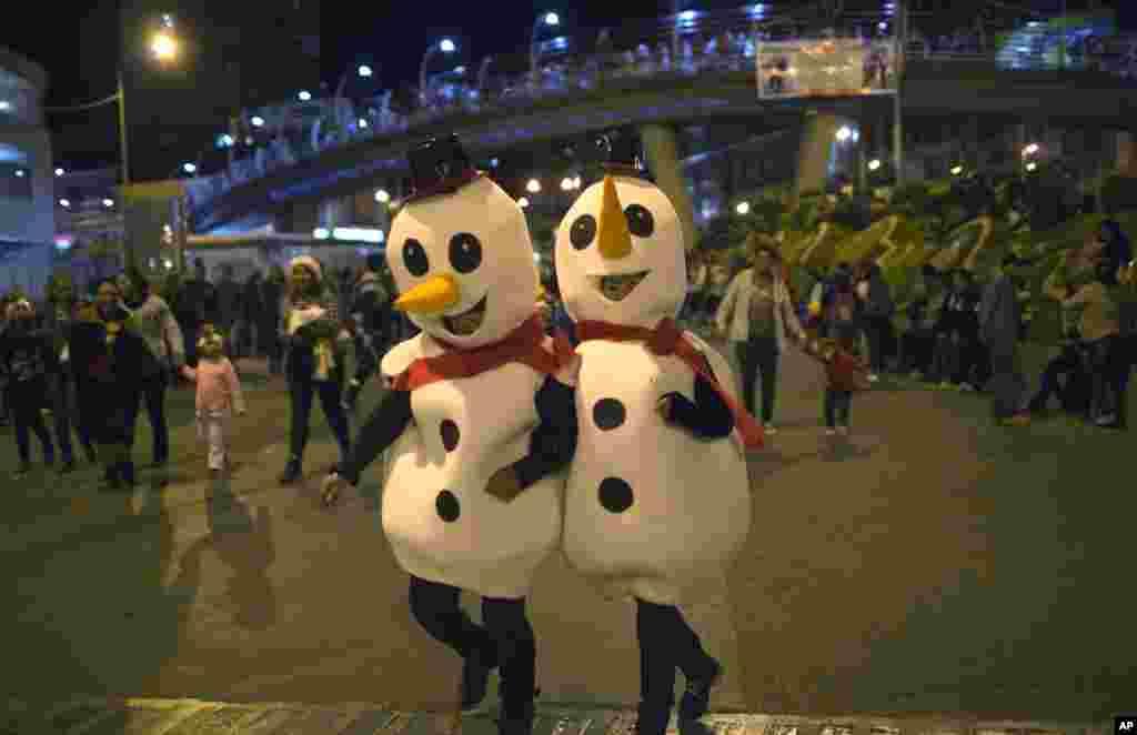 دو شرکت کننده زن با پوشیدن لباس به شکل آدم برفی در رژه سالانه کریسمس در بولیوی