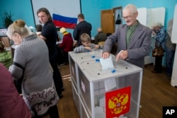 FILE - A Russian casts his ballot at a polling station in Kostroma, Sept. 13, 2015. A recent Levada Center poll showed declining support for the ruling party as the Sept. 18 parliamentary elections approach..