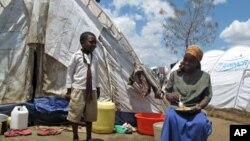 一名流離失所的婦女和男孩在肯尼亞的臨時住所前(2008年4月資料照)