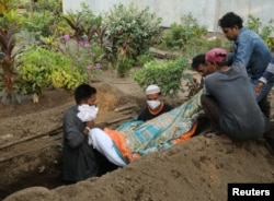 Gayesh Ansari, looks at the body of his 8 months pregnant wife, Gulshan Ansari as he lowers her body into a grave after she died from the coronavirus disease (COVID-19) at a graveyard in Mumbai, India April 28, 2021. Picture taken April 28, 2021. REUTERS/